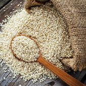 image of sesame seed  - sesame seeds in wooden spoon and in sack on wooden rustic table top view - JPG
