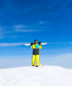 stock photo of snowboarding  - Snowboarder hold snowboard on top of hill - JPG