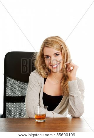 Happy woman sitting at the desk with a cup of tea.