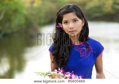 Young Vietnamese woman in blue Ao Dai holding orchid flowers while Looking at the Camera.