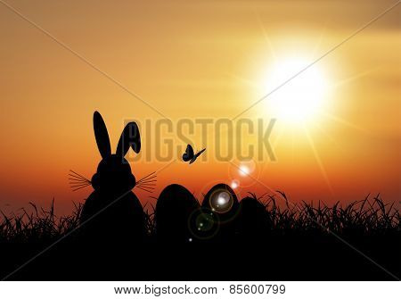 Silhouette of the Easter bunny sat in the grass against a sunset sky