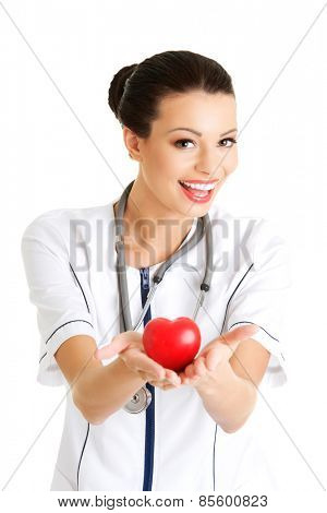 Female doctor with stethoscope holding heart model.
