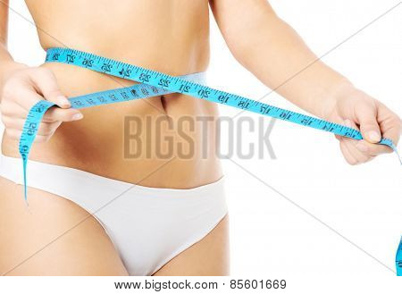 Close up on woman measuring her waist.