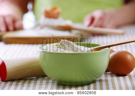 Young woman prepares dough on table close up