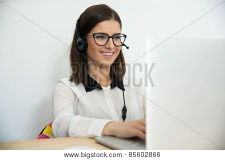 Happy female support operator in headset working on the laptop
