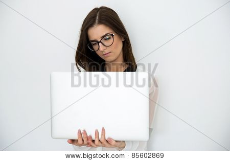 Young beautiful woman standing with laptop over gray background