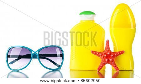 Bottles of suntan cream with sunglasses and sea star isolated on white