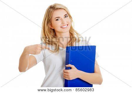 Young woman pointing on her binder.
