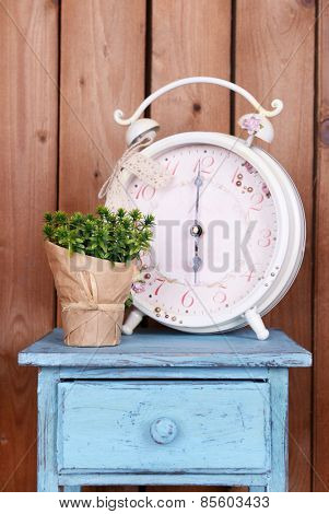 Interior design with big alarm clock and plant on tabletop on wooden planks background