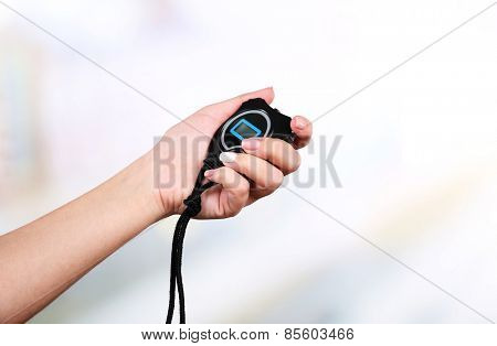 Electronic sport timer in  female hand on bright blurred background