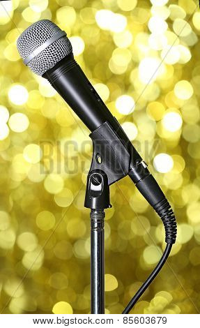 Microphone on stand on golden background
