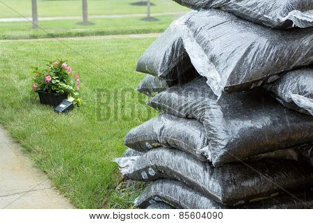 Stacked Plastic Bags Of Mulch And Flowers In Rain
