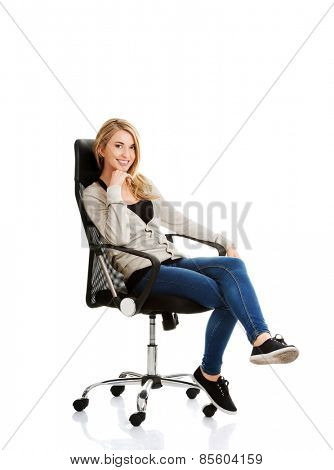 Young woman sitting on armchair touching chin.