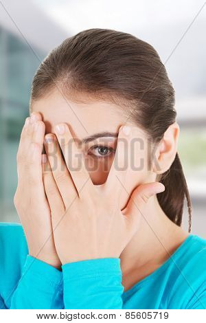 Shy teenage girl peeking through covered face.
