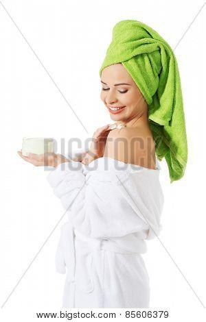 Woman in bathrobe applying cream on shoulder.
