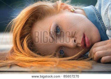 Fashion portrait of strict red-haired girl, close up.