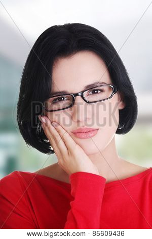 Young woman with huge toothache