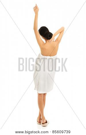 Back view woman wrapped in towel stretching arms.