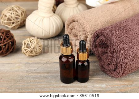 Beautiful spa composition with aromatic oil and massage bags on wooden background
