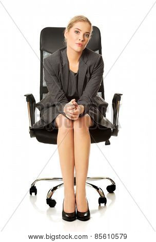 Confident businesswoman sitting on armchair, looking at the camera.