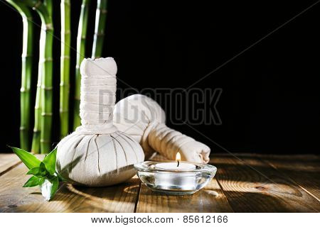 Beautiful composition with massage bags and candle on table on dark background