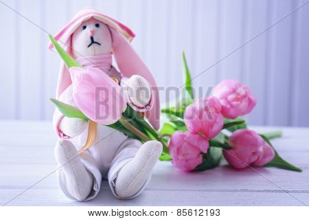 Beautiful pink tulips with toy on wooden background