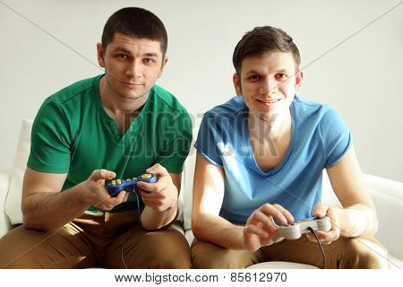 Two handsome young men playing video games in room