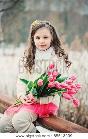 spring vertical outdoor portrait of beautiful child girl with tulip flowers