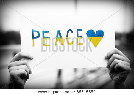 Hands holding paper with Peace of Ukraine
