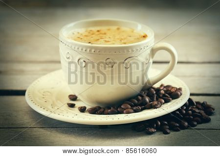 Cup of coffee on wooden table, close up