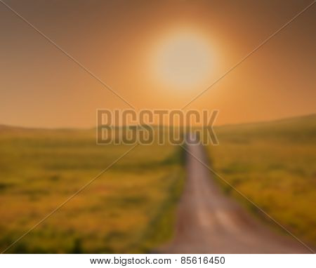Abstract blurred background of a rural road climbing towards sunrise