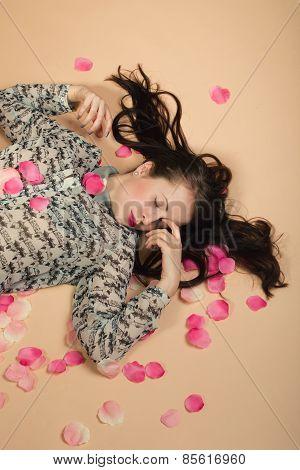 Atractive Brunette Girl Lying On Beige Background