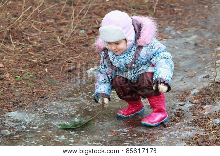 Little girl exploring icy puddle