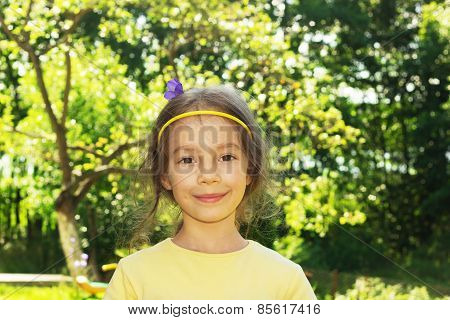 Beautiful smiling little girl on background of city park.