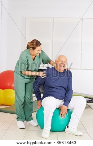 Senior man with aching back sitting in physical therapy on a gym ball