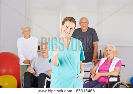 Happy physiotherapist holding thumbs up in front of a senior group in a nursing home