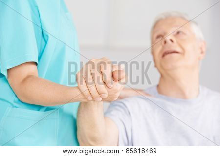 Nursing assistant holding hand of senior man for support