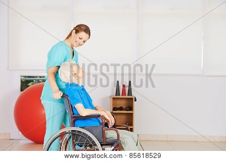 Caregiver dring senior woman in wheelchair to physiotherapy