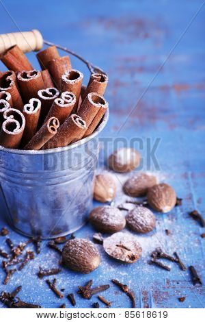 Cinnamon sticks in metal bucket, nutmeg and cloves on color wooden table background