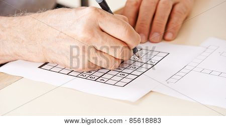 Hand of senior man solving sudoku quiz with a pen