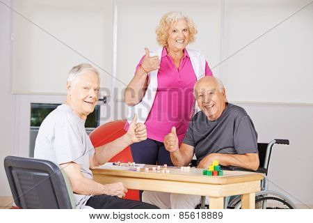 Three happy senior people in nursing home holding thumbs up and playing Bingo