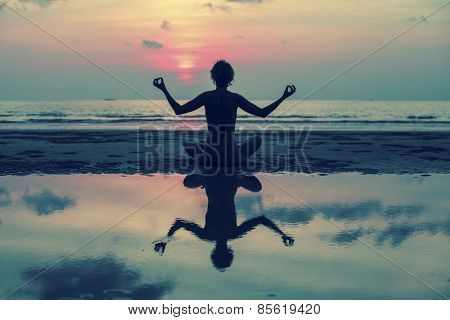 Yoga silhouette. Girl doing meditation in the ocean beach. With reflection in water.