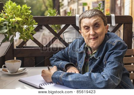 Disabled man with palsy, smiling sitting at an outdoor cafe.