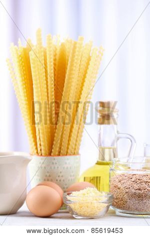 Pasta with olive oil, eggs, cheese and flour on wooden table on curtain background