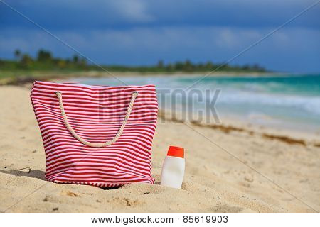bag and suncream on tropical beach