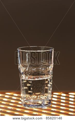 Glass of clean mineral water on lattice surface and dark color background
