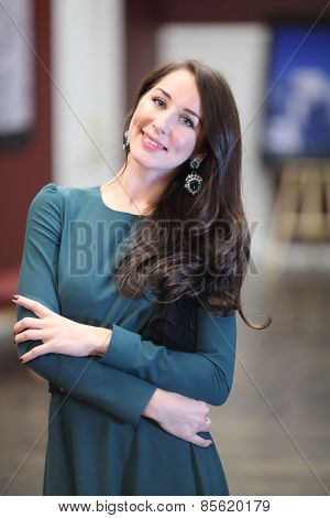 Portrait of a beautiful young woman with dark long hair in a green evening dress