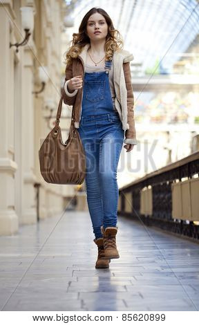 Young girl walking in denim overalls in the shop