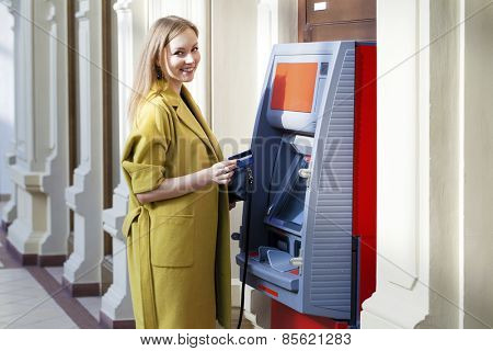 Blonde lady using an automated teller machine . Woman withdrawing money or checking account balance
