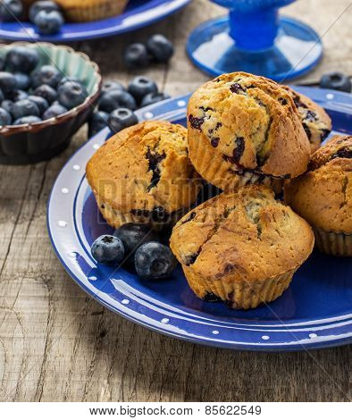 Homemade muffins with blueberries on a wooden background